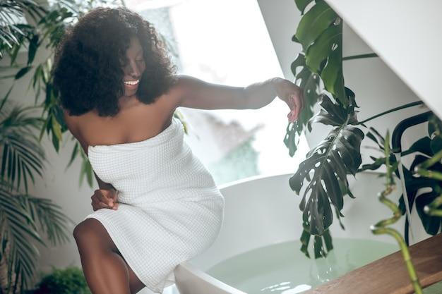 Czas się zrelaksować. uśmiechnięta ciemnoskóra, dość długowłosa kobieta w nagich ramionach, siedząca na wannie, dotykająca wody