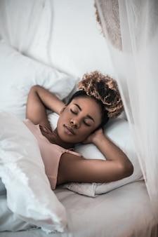 Czas spać. młoda dorosła piękna ciemnoskóra kobieta leży spokojnie z zamkniętymi oczami w łóżku wkładając ręce pod głowę