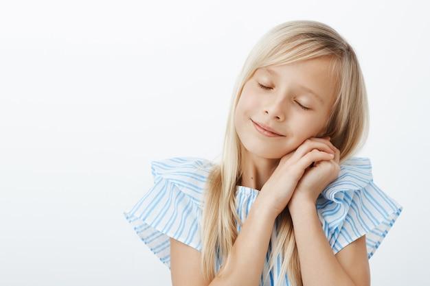 Czas spać. śpiąca śliczna mała europejska dziewczyna o blond włosach, zamykających oczy i opierająca się na dłoniach, jakby spała, czująca się zadowolona i zmęczona po spędzeniu niesamowitego czasu z przyjaciółmi na szarej ścianie