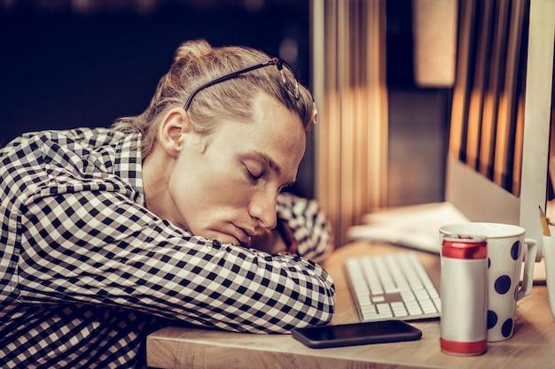 Czas spać. wyczerpany pracownik biurowy z zamkniętymi oczami marząc o wakacjach