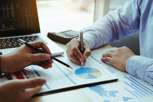 Czas spotkania biznesowego. wykres kosztów analizy ludzi biznesu na biurku w sali konferencyjnej.