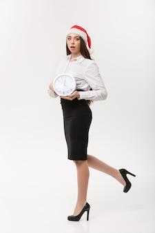 Czas szczytu concept - piękna młoda kobieta kaukaski działa z zegarem na białym tle.
