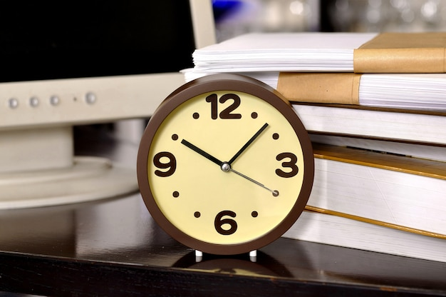 Czas szkolny. budzik i stos książek. pojęcie edukacji.