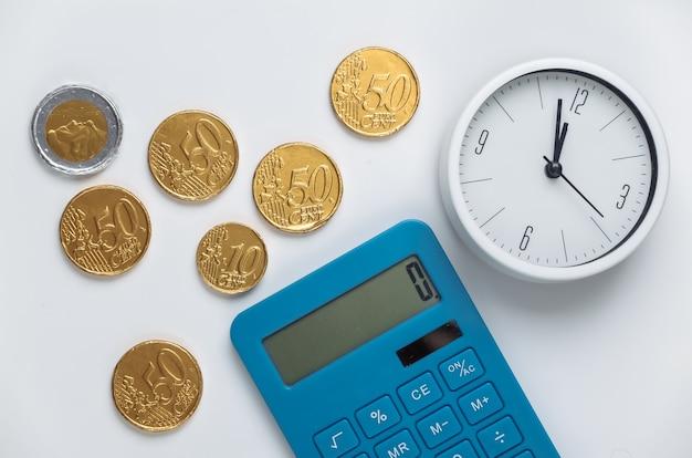 Czas to pieniądz. zegar z kalkulatorem i monetami na białym