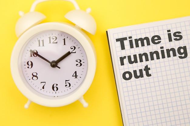 Czas ucieka - fraza na notatniku z białym budzikiem na boku na żółtym tle.