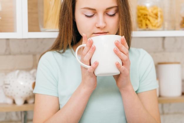 Czas wolny. domowa przytulność. piękna młoda kobieta z filiżanką ulubionego napoju.