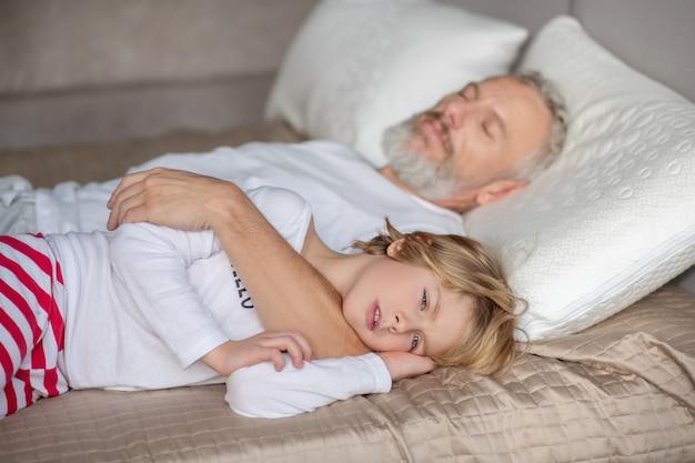 Czas wolny. śpiące dziecko, które włożyło rękę pod głowę i przytuliło go siwowłosego śpiącego tatę w domu na łóżku