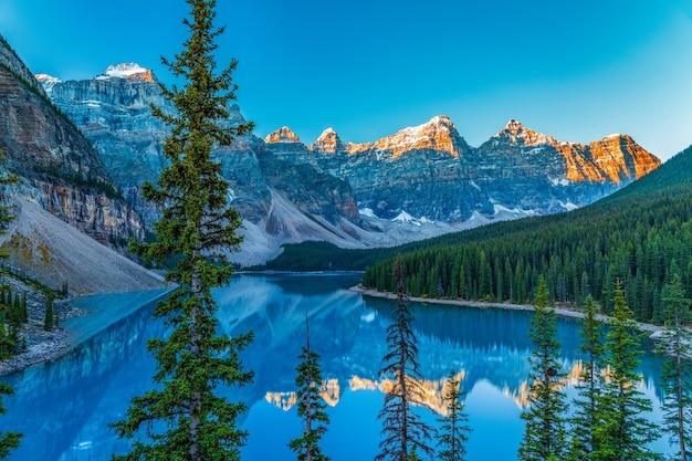 Czas wschodu słońca nad jeziorem morenowym w słoneczny letni dzień. dolina dziesięciu szczytów zmienia kolor na czerwony i odbija się na turkusowej powierzchni wody.
