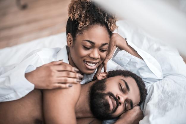 Czas wstawać. młody dorosły szczęśliwy ciemnoskóra kobieta dotykając ręką do spania brodaty mężczyzna w łóżku