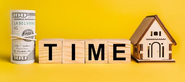 Czas z miniaturowym modelem domu i pieniędzmi na żółtym tle. pojęcie biznesu, finansów, kredytu, podatków, nieruchomości, domu, mieszkania
