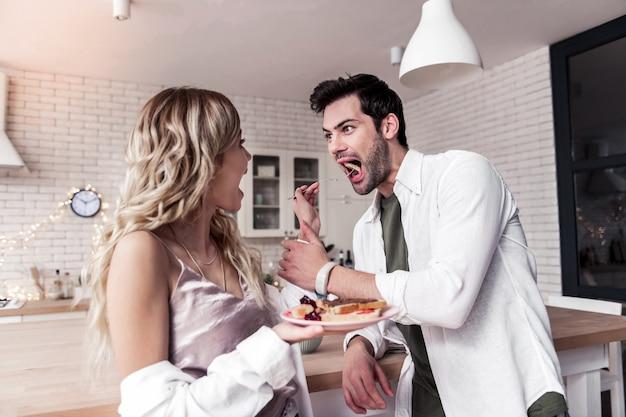 Czas zabawy. ciemnowłosy brodaty mężczyzna ubrany w białą koszulę i jego żona bawiąca się przy śniadaniu