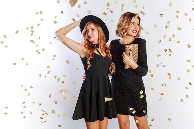 Czas zabawy dwóch najlepszych przyjaciół, blond kobiety w eleganckiej sukni czarny koktajl pozowanie studio na białym tle. błyszczące złote konfetti. falowana fryzura.