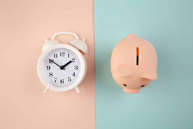 Czas zainwestować. biały zegar i skarbonka na różowym niebieskim pastelu.