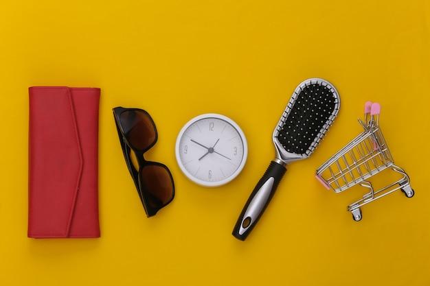Czas zakupów. akcesoria damskie. portfel, grzebień, okulary przeciwsłoneczne i zegar, wózek w supermarkecie na żółto.