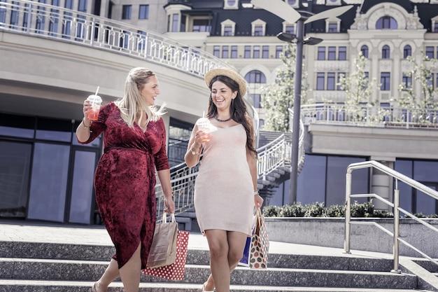 Czas zakupów. pozytywne miłe kobiety trzymające torby idąc z centrum handlowego