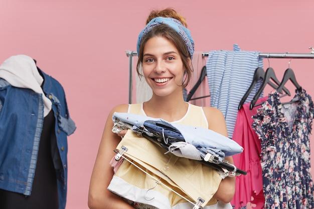 Czas zakupów. radosna młoda europejka trzymająca wieszaki z modnymi ubraniami i szeroko uśmiechnięta, ciesząca się zakupami wiadomości. szczęśliwa kobieta zbiera letnie ubrania podczas pakowania jej torby, jadąc do podróży