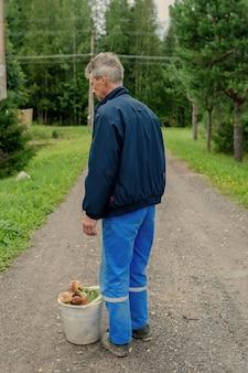 Czas zebrać grzyby. człowiek z białym wiadrem grzybów w jesiennym lesie.