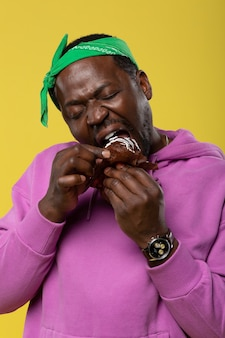 Czas zjeść. skoncentrowany mężczyzna z zamkniętymi oczami i gryzący kawałek babeczki