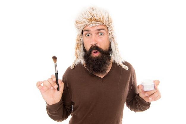 Czasami moda staje się dziwna. a jeśli dodasz makijaż. stylista mody brodaty mężczyzna nosić futrzany kapelusz trzymać pędzel do nakładania makijażu. pielęgnacja twarzy. najnowsze trendy w modzie. ekscentryczny freak facet na białym tle.