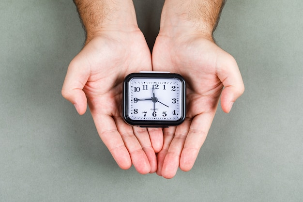 Czasu zarządzanie i zegarowy cykot pojęcie z zegarem na szarego tła odgórnym widoku. trzymając się za ręce zegar. obraz poziomy