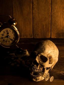 Czaszka jest umieszczona na drewnianym stole, tył czaszki to narkotyk i zegar.