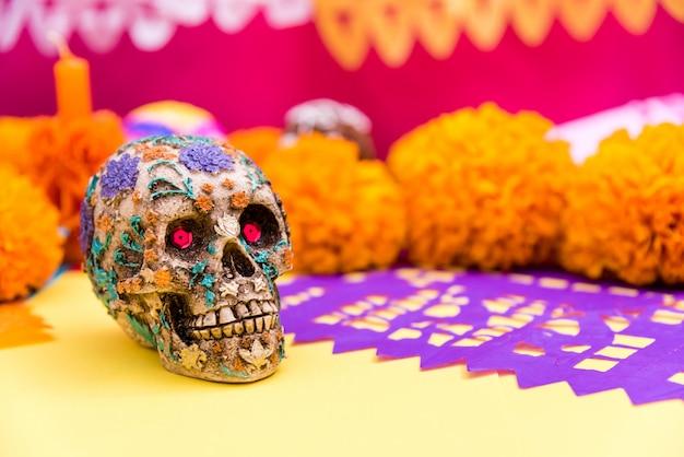 Czaszka, posiekany fioletowy papier i kwiaty cempasuchil przy ołtarzu, święto zmarłych