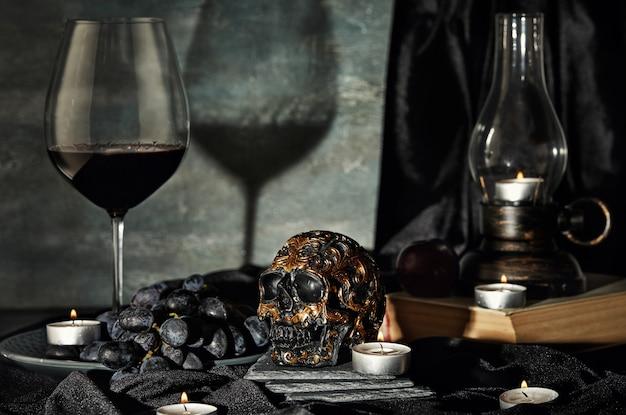 Czaszka, świece, wino, winogrona, stara lampa w ciemności. halloween