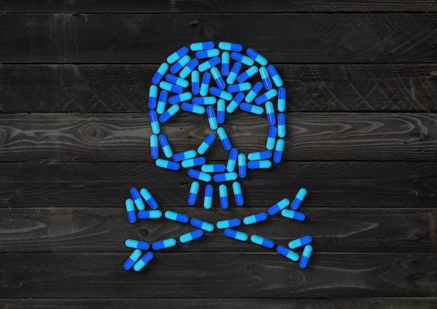 Czaszka wykonana z niebieskich tabletek kapsułki na białym tle na czarnym tle drewna. ilustracja 3d