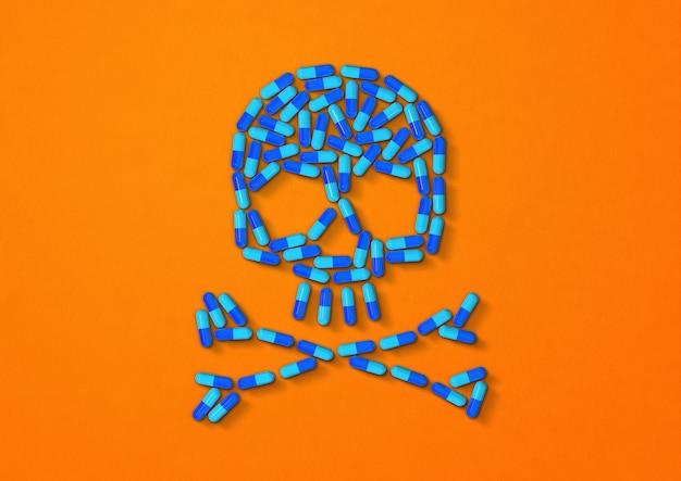 Czaszka z pigułki niebieskie kapsułki na białym tle na pomarańczowym tle. ilustracja 3d