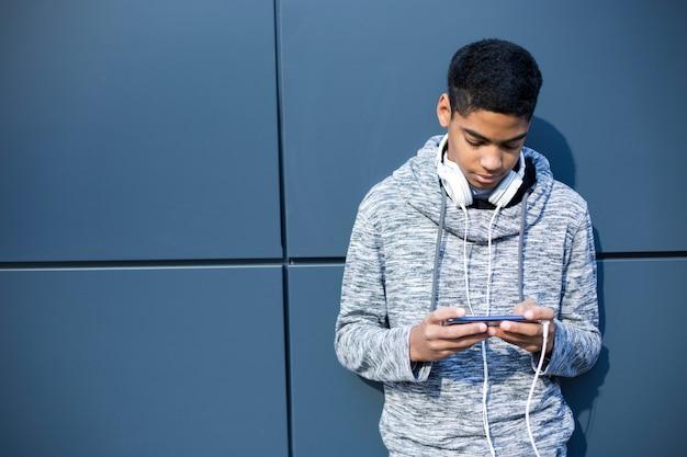 Czat online. nastolatek afroamerykanów używa do komunikacji telefonu komórkowego.