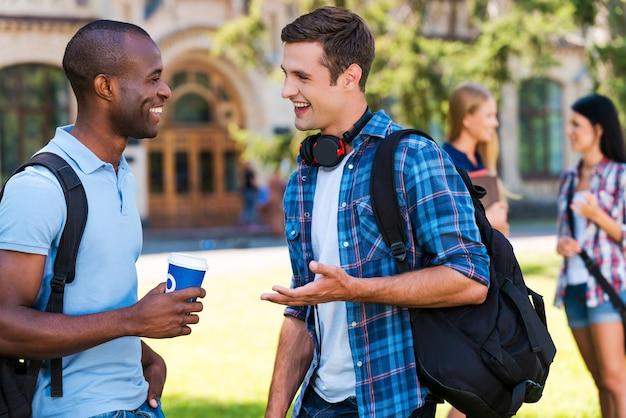 Czatować z przyjaciółmi. dwóch młodych mężczyzn rozmawiających ze sobą i uśmiechających się, podczas gdy dwie kobiety stoją w tle