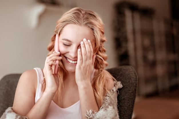 Czatowanie przez telefon. żartobliwa jasnowłosa dama z dwoma warkoczami zamykającymi twarz z powodu przezabawnego dialogu z przyjaciółką