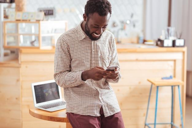 Czaty poprawiające nastrój. wesoły miły młody człowiek oparty na stole w kawiarni i wysyłający wiadomości tekstowe do swoich przyjaciół przez telefon, uśmiechając się radośnie
