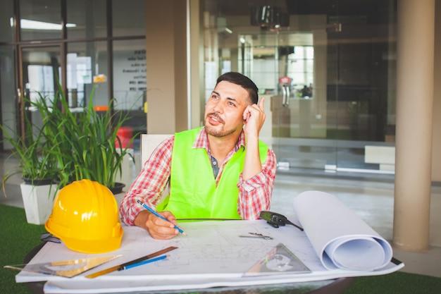 Czeka na inspirację. inżynierowie siedzą i myślą o pracy, odwracają wzrok, siedząc w swoim miejscu pracy.