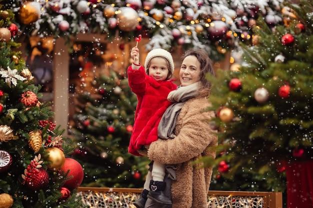 Czekając na wakacje noworoczne. wesoła mama z dziećmi na spacerze zimą po ozdobionej bożonarodzeniowej ulicy.
