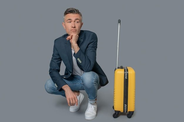 Czekający mężczyzna przykucnął w pobliżu walizki podróżnej