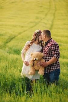 Czekam kochanie. rodzicielstwo. ciężarna młoda kobieta i jej mąż są szczęśliwi całować i trzymać misia w rękach, iść w plenerowym w polu zielona trawa, selekcyjna ostrość.