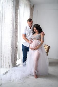 Czekam na dziecko. niesamowita para pozuje mąż i ciężarna żona