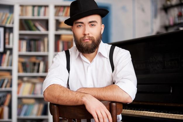 Czekam na inspirację. portret przystojnych młodych brodatych mężczyzn siedzących przed fortepianem