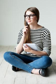 Czekam na inspirację. rozważna młoda kobieta w pasiastym ubraniu, trzymająca notatnik i dotykająca podbródka długopisem, siedząc na drewnianej podłodze