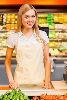 Czekam na klientów. piękna młoda kobieta sprzedawca uśmiecha się do kamery stojąc w sklepie spożywczym