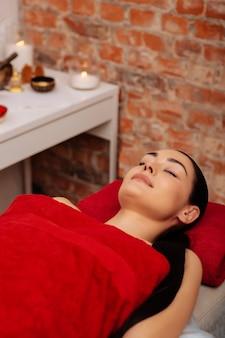 Czekam na procedurę. piękna spokojna sprawna kobieta leżąca nago na łóżku medycznym w wyposażonej szafce spa