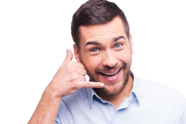 Czekam na twój telefon. pewny siebie młody człowiek w koszuli, gestykulując telefonem komórkowym w pobliżu twarzy i uśmiechając się, stojąc na białym tle