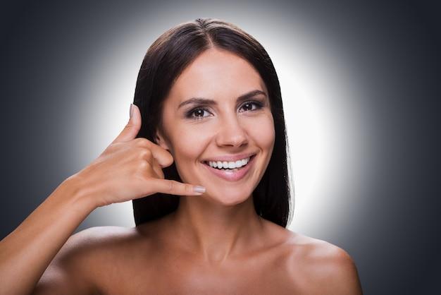 Czekam na twój telefon! portret uśmiechniętej młodej kobiety bez koszuli, patrząc na kamerę i gestykulując telefon komórkowy w pobliżu jej twarzy, stojąc na szarym tle