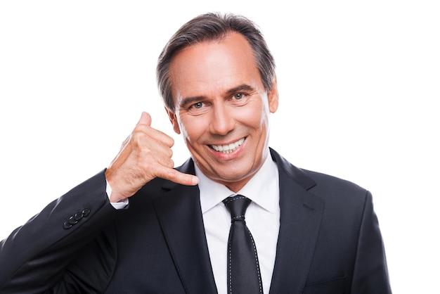 Czekam na twój telefon. szczęśliwy dojrzały mężczyzna w formalwear gestykuluje telefonem komórkowym w pobliżu twarzy i uśmiecha się stojąc na białym tle
