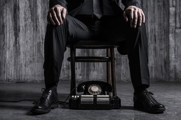 Czekam na ważny telefon. zbliżenie: apodyktyczny mężczyzna w formalnej odzieży siedzącej na krześle ze staromodnym telefonem leżącym u jego stóp