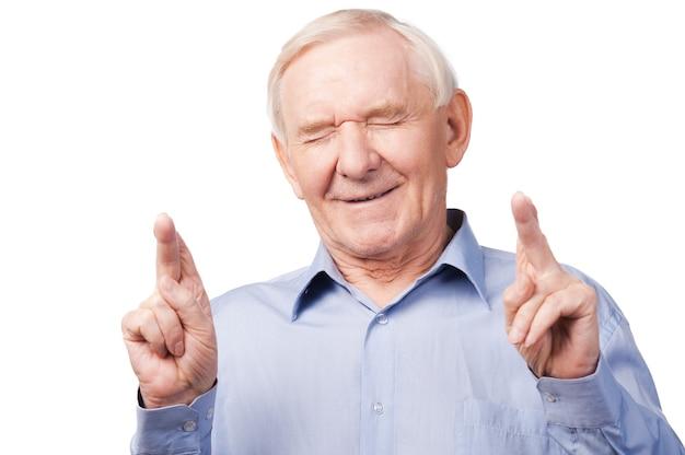 Czekam na wyjątkową chwilę. portret starszego mężczyzny w koszuli trzymającego skrzyżowane palce i zamknięte oczy, stojąc na białym tle