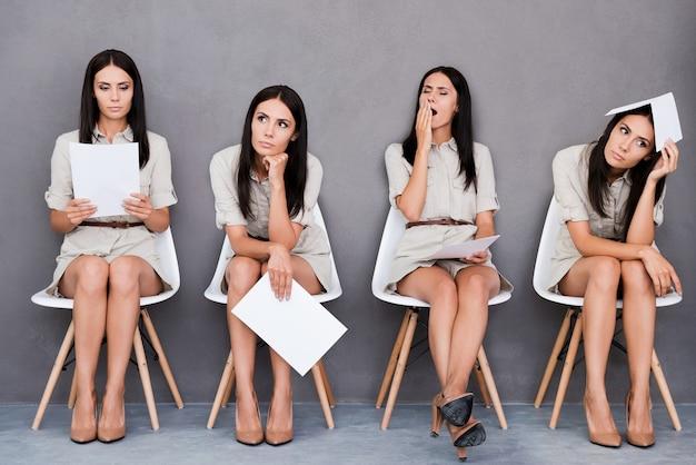 Czekam na wywiad. cyfrowy kompozyt młodej bizneswoman wyrażającej różne emocje, trzymając papier i siedząc na krześle na szarym tle