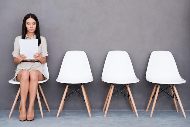 Czekam na wywiad. pewna siebie młoda kobieta trzymająca papier siedząc na krześle na szarym tle