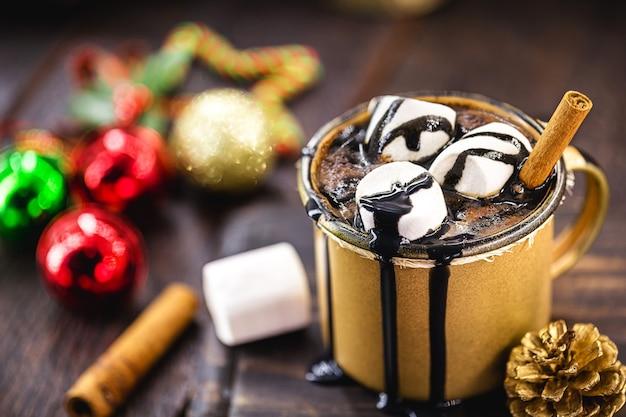 Czekolada i gorące kakao z pianką marshmallow w złotym ceramicznym kubku w otoczeniu świątecznych rzeczy na rustykalnym drewnianym stole